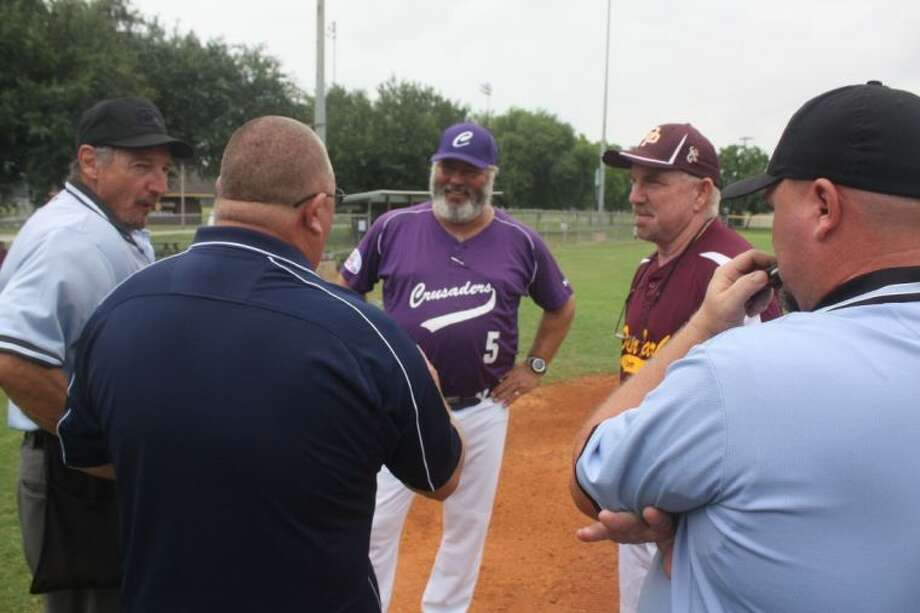 Pony South Zone Director Billy Brooks (Navy-colored shirt) goes over the ground rules with Deer Park's and Cen-Tex's managers plus the umpires at home plate prior to a Friday game. Photo: Robert Avery