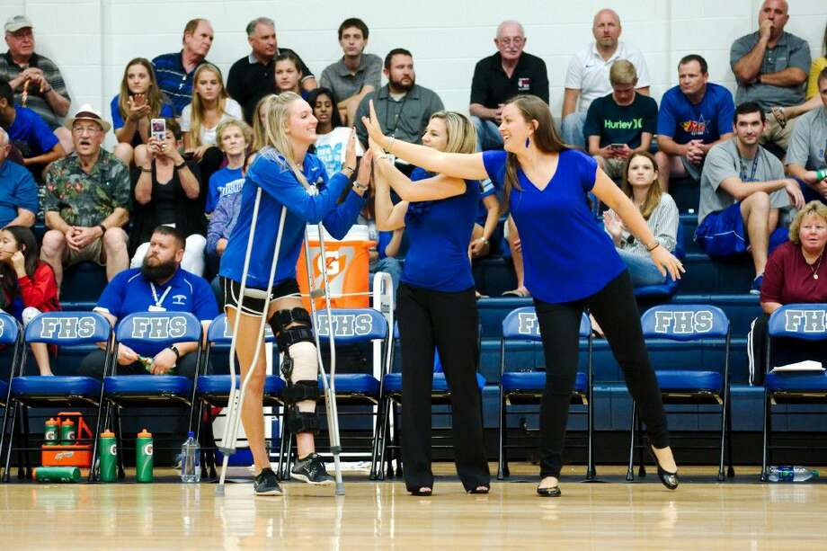 Friendswood's Kelly Colwell, shown here getting high fives from coaches Shayna Sauers (center) and Sarah Paulk, is an inspiration to her teammates following a season-ending injury. Photo: Kirk Sides