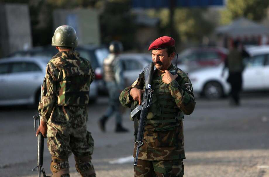 Afghan soldiers inspects the site of suicide attack In Kabul near Afghanistan's Defense Ministry, Monday. Twin bombings near the Afghan Defense Ministry have killed dozens of people in an attack claimed by the Taliban.