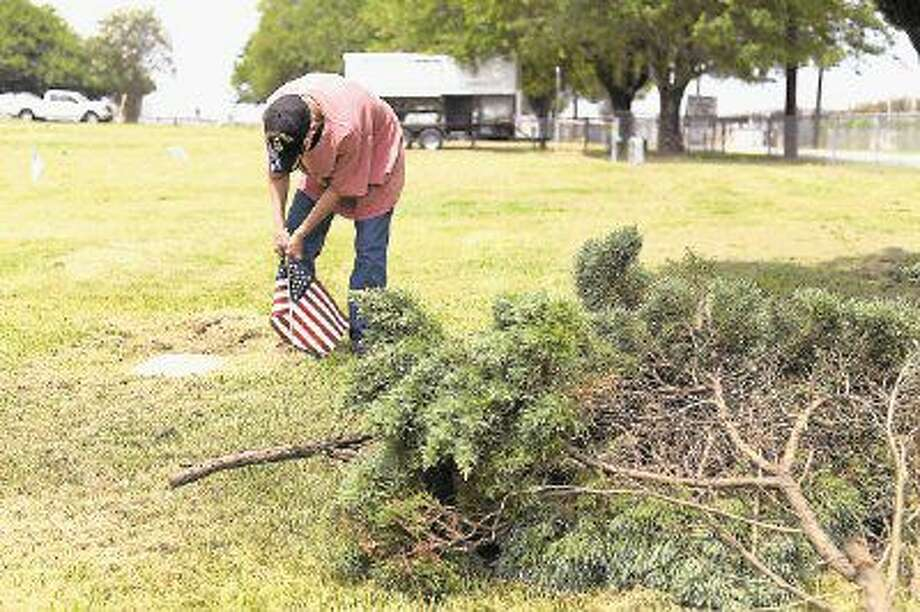 Ronnie Bufford spends much of a recent Saturday afternoon placing American flags on the markers of veterans buried at Crown Hill Cemetery in Pasadena.
