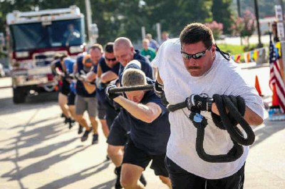 Firefighter Chris Mitcham, of The Woodlands Fire Department, leads a team of fellow firefighters in the fire truck pull event benefiting the Special Olympics Texas on Saturday at Armstrong Elementary School in Conroe. Photo: Michael Minasi