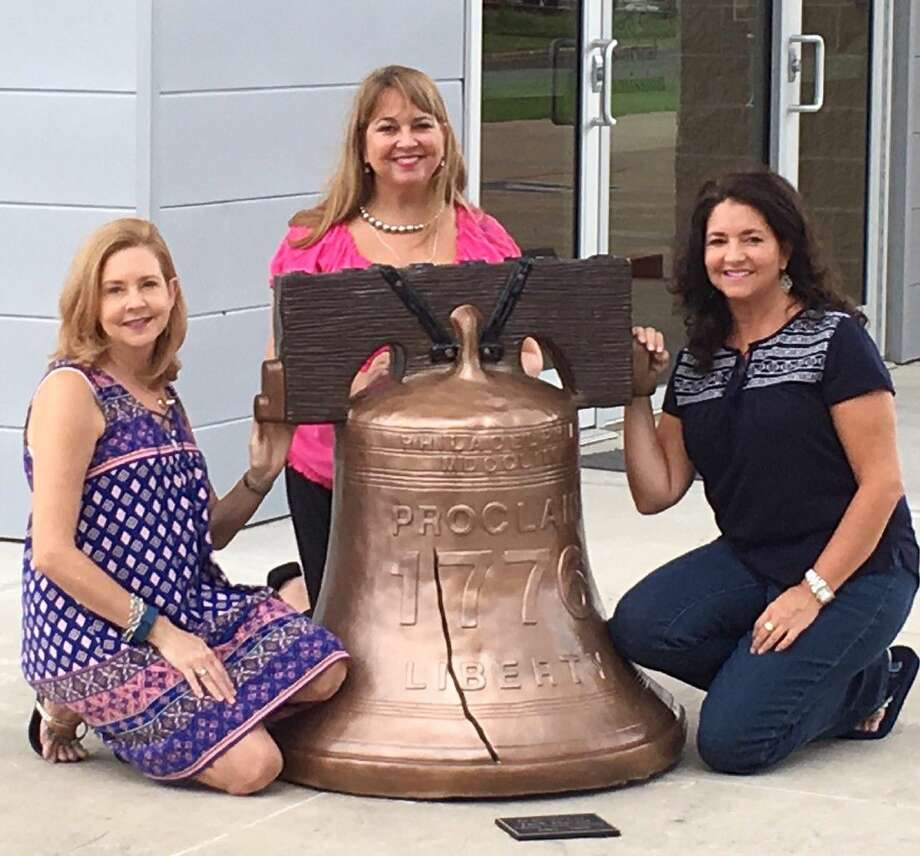 The three daughters of the late Liberty County Attorney Jack Hartel are shown with the Liberty Bell in front of the building at 318 San Jacinto Ave. in Liberty that bears their father's name. Pictured left to right are Angie Patterson, Jackie Hartel Smith and Laurie Vaught. Photo: Submitted