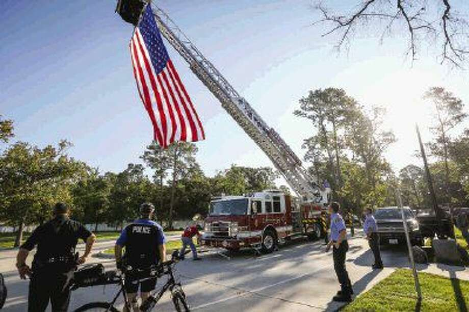 First responders and veterans gather to watch as a U.S. flag is raised on the ladder of a Conroe fire engine during the Patriots Day ceremony on Sunday at VFW Post 4709 of Conroe. To view more photos from the event, go to HCNPics.com. Photo: Michael Minasi