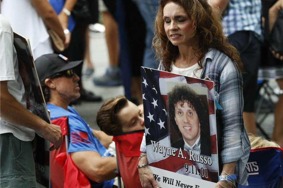 A mourner holds a photo of her loved one during the 15th anniversary of the attacks of the World Trade Center at the National September 11 Memorial Sunday in New York.