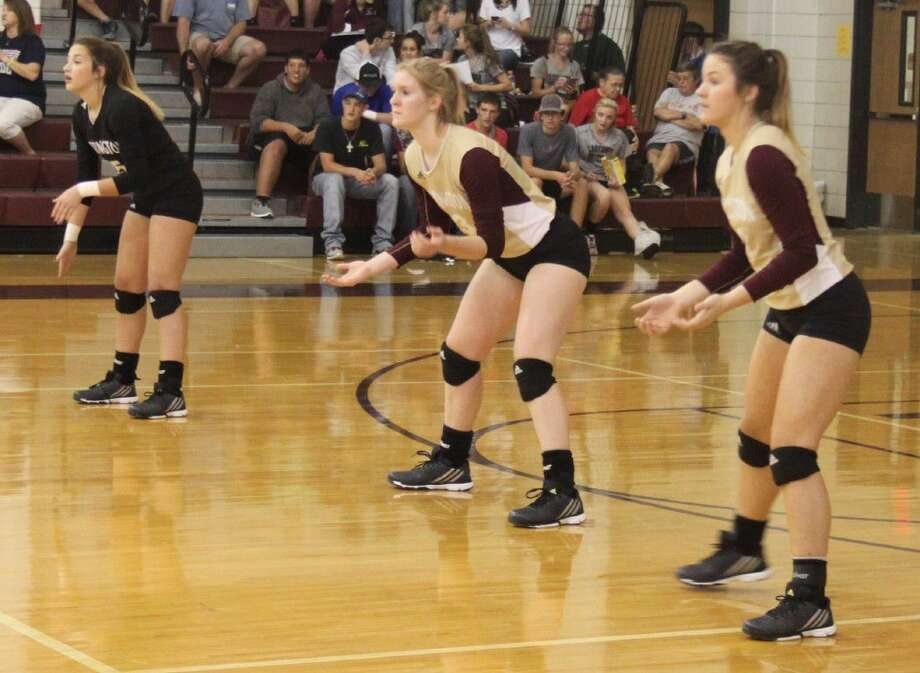 Chloe Mullins (left), Claire Chapman (middle) and Becca Rasberry (right) of the Tarkington LadyHorns prepare to defend against the serving Lady Patriots. Photo: Jacob McAdams