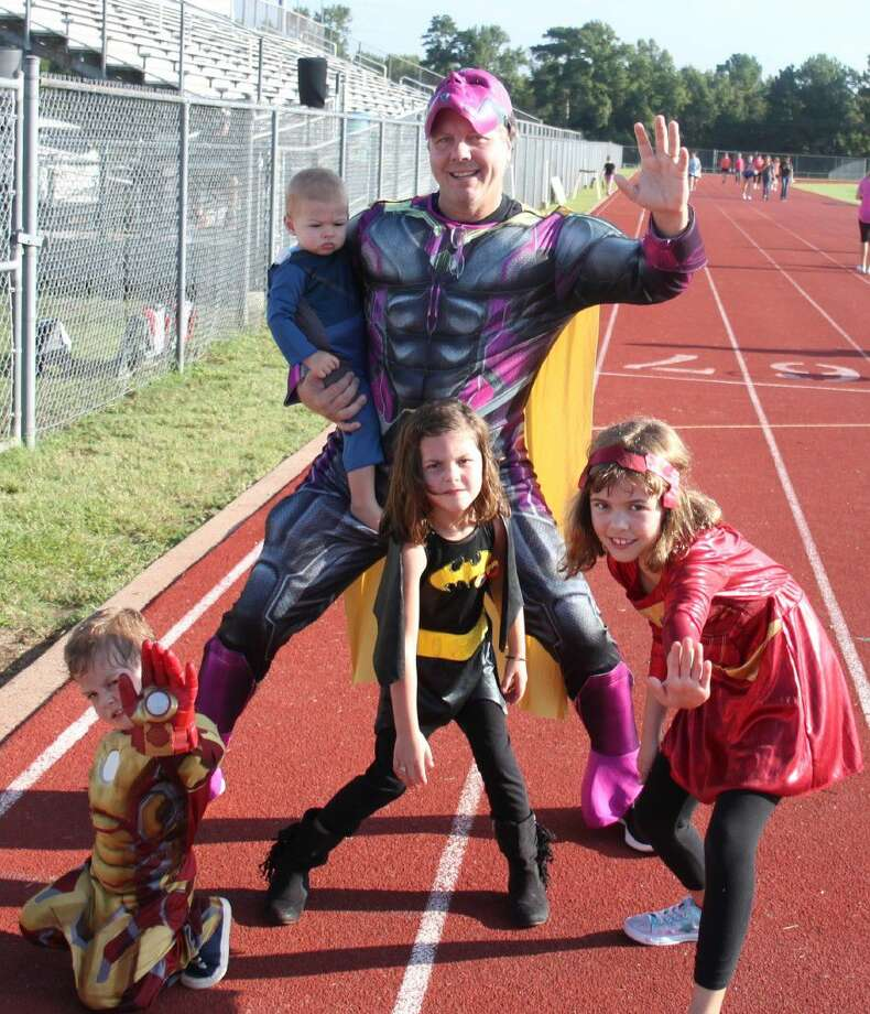 Coldspring-Oakhurst Principal Todd White (back) greets newcomers as the superhero known as the Vision along with his children. Pictured are (back row) Keira White as Miss Fantastic and Todd White as the Vision; (front row) Coulter White as Iron Man, Lyla White as Batgirl and Madison White as Iron Girl. Photo: Jacob McAdams