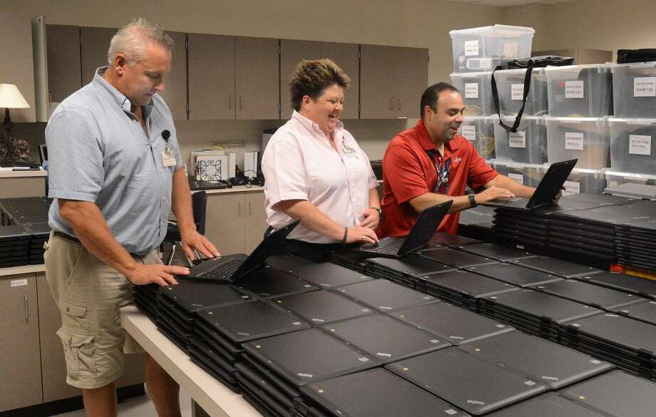 Craig Gentry, Klein ISD Manager Technology Services, Karen Fuller, Chief Technology Officer, and Philip Perez, Supervisor Technical Services, examine some of the 1.500 laptop computers that were given to students at Klein ISD's Ulrich Intermediate School. Photograph by David Hopper Photo: Z-David Hopper