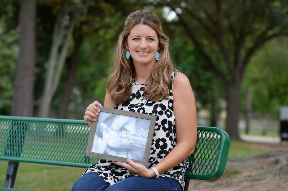 Dallas Ledger, a volunteer for Angel Gowns By Diane, holds a photo in honor of her stillbirth baby at Mary Jo Peckham Park in Katy on Sept. 9. Photo: Staff