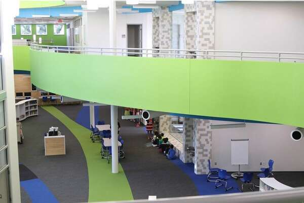 """At Condit Replacement Elementary, another theme the design team was inspired by was the shape of a ribbon. To show this, a ribbon of classrooms is threaded through the open concept library called the """"learning commons."""" The commons freely allows students to roam the stacks of books and technology tools."""