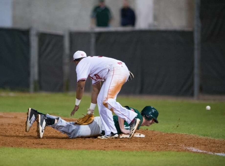 A St. Thomas first baseman watches a pickoff throw get away during the Eagles recent game against Strake Jesuit. The Eagles will be one of the hosts of their annual Father Wilson/Sister Julia tournament, which begins Thursday morning at four different sites on the north side of the city. Photo: Kevin B Long