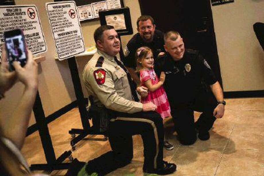 Officers Kelly Kennerly and Steven Helton, both of Oak Ridge North Police Office, and deputy Zachary Vercher, of the Montgomery County Sheriff's Office, pose for photos with Lila Alexander on Monday at Oak Ridge North City Hall. Photo: Michael Minasi
