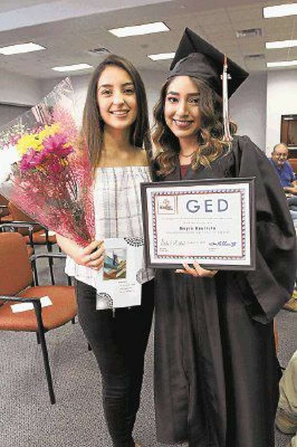 Sixteen students of the Adult Reading Center received their GED certificate at a graduation ceremony in August at the Pearland ISD Support Center,1928 N Main Street. Alondra Bautista, left, holds flowers for her aunt, Mayra Bautista, who received her GED certificate. A gala to benefit the center is scheduled for Oct. 8 at the Knights of Columbus Hall in Pearland. Photo: Suzanne Rehak