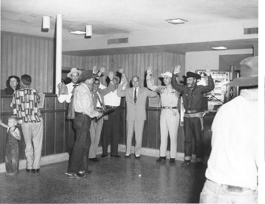 This might seem like a bank holdup until you see the grins on the victims' faces and the unconcerned child near the masked gunman. The faux robbery in the 1950s was held to publicize the Pasadena rodeo.