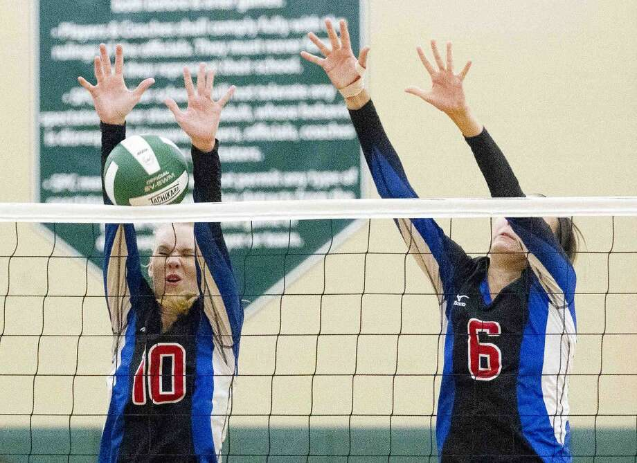 Oak Ridge's Hannah Mikelonis (10) and Hailey Lohnes (15) block a shot during the first set of a non-district volleyball game Tuesday, Sept. 13, 2016, at The John Cooper School. Oak Ridge swept John Cooper 3-0. Go to HCNpics.com to view more photos from the game.
