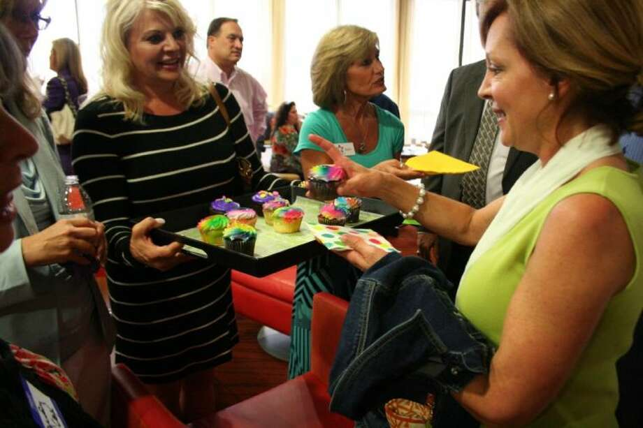 Kyle Campbell receives a cupcake from Danelle Fields at the New Caney Independent School District Education Foundation's two-year celebration. Photo: Nate Brown