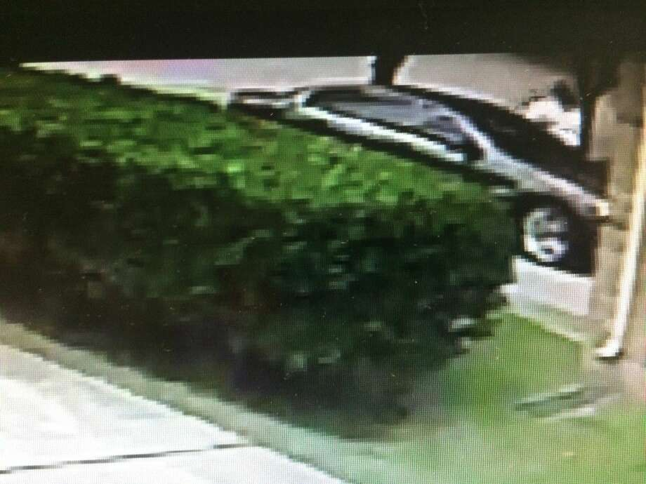 A still-shot from surveillance footage of the suspect wanted for burglary in the 4500 block of Jaymar Drive in the New Territory subdivision, seen next to his vehicle in the upper righthand corner. Photo: Fort Bend County Crime Stoppers