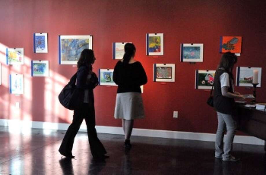 Visitors walk around and view the children's art work at the opening of the Making a Mark exhibit. Photo: Jazmin Rodriguez