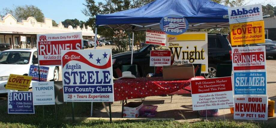 """A booth sits across the street from the Elections Administrations Building with signs from both Democratic and Republican candidates. Haney Wilkerson is also holding a sign being handed out by the Republican Party that reads """"Proud member of the Obama team"""" with an arrow pointed to the right, meant to be placed against the signs of Democratic candidates. Photo: Jacob McAdams"""