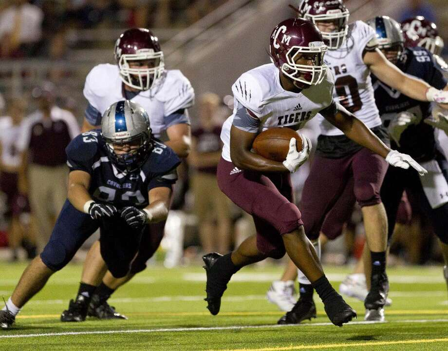 A&M Consoliated running back Tre' Newton (5) runs the ball past College Park defensive linemen Austin Fox (83) during the second quarter of a non-district high school football game Thursday.