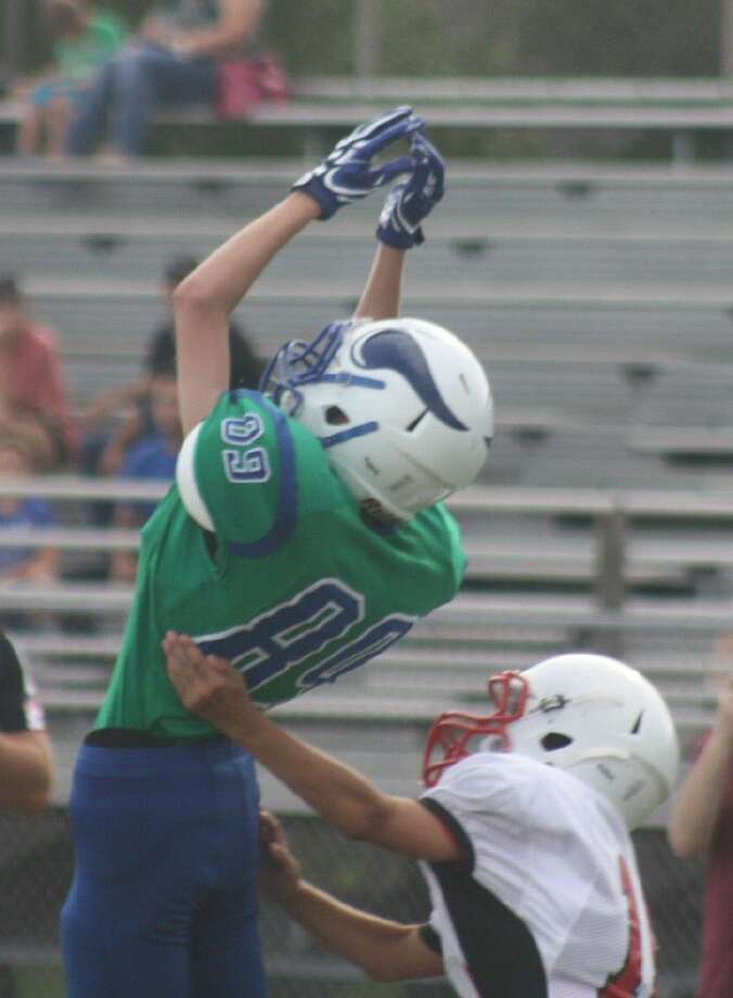 Fairmont Junior High's Brett Hiller leaps up in his attempt to grab a pass but was unsuccessful. Back in the first quarter, Hiller had an interception and returned it for a touchdown. Photo: Robert Avery