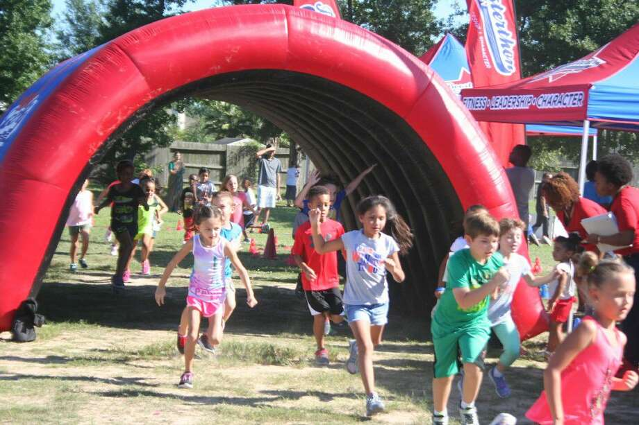 Fall Creek Elementary students run through one of the inflatable archways during the Boosterthon fun run Sept. 15.