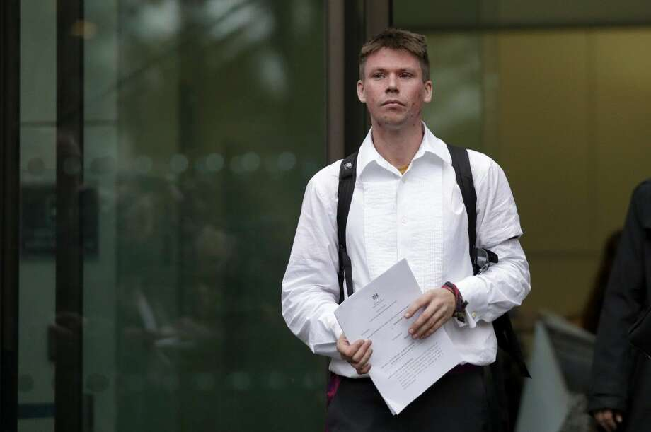British national Lauri Love, who is accused of hacking into U.S. government computers, holds a copy of the extradition application papers as he leaves after the ruling that he should be extradited, outside Westminster Magistrates' Court in London.