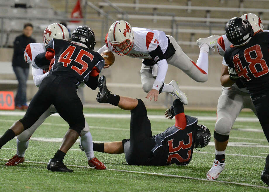 Memorial's Matthew Jordan leaps over Langham Creek players during the teams' bi-district playoff game on Friday. Photo: Joel Weckerly