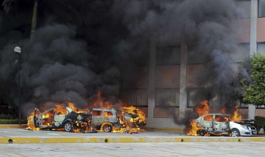 Cars burn in front of the state congress building after protesting teachers torched them on Nov. 12 in the state capital city of Chilpancingo, Mexico.