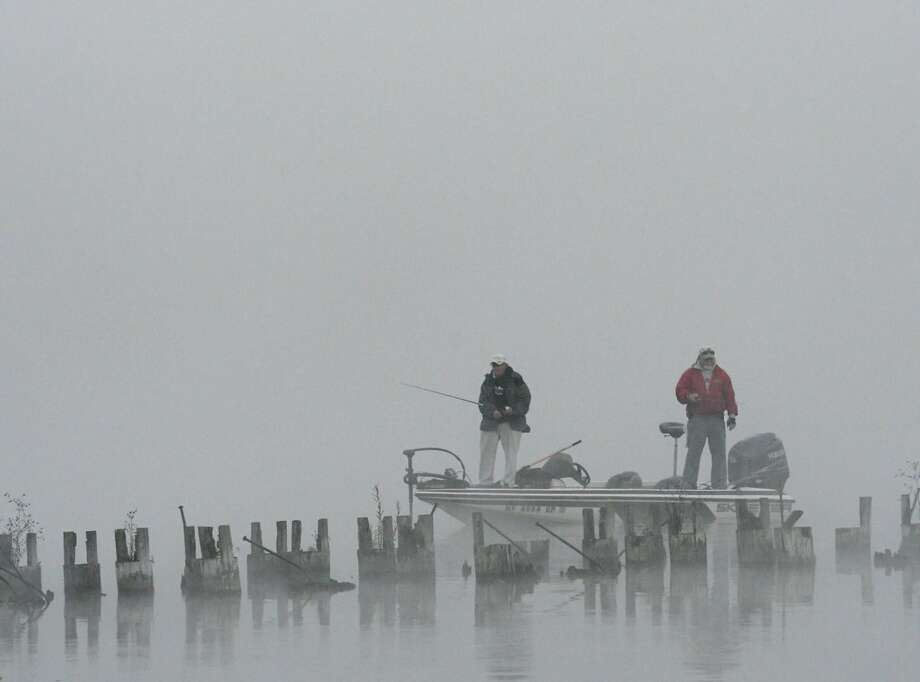 Two men fish in Saratoga Lake Friday morning. Fog covered much of the Capital Region's low-lying areas but it was expected to burn off as sun's heat grows more intense. (Skip Dickstein / Times Union)