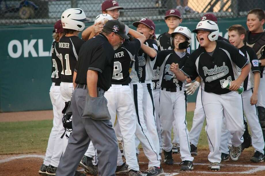 Teammates swarm Pearland's Matthew Adams (13) after he hits a home run in the first inning of the semi-final game against Mississippi Tuesday, Aug. 5. Photo: KIRK SIDES