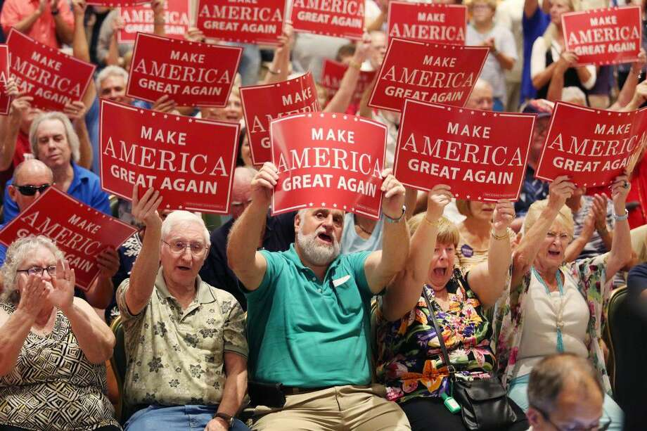 Donald Trump supporters wave signs at a campaign rally at The Villages, Fla., on Saturday