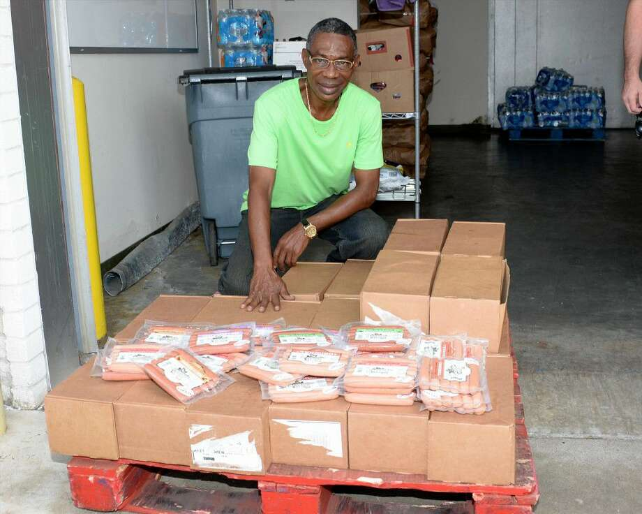 Chris Samuels, director of Heavenly Hands, examines a donation of hot dogs made by Holmes Smokehouse at Bethel's Place Empowerment Center in Houston on Friday, Sept. 16. Photo: Craig Moseley