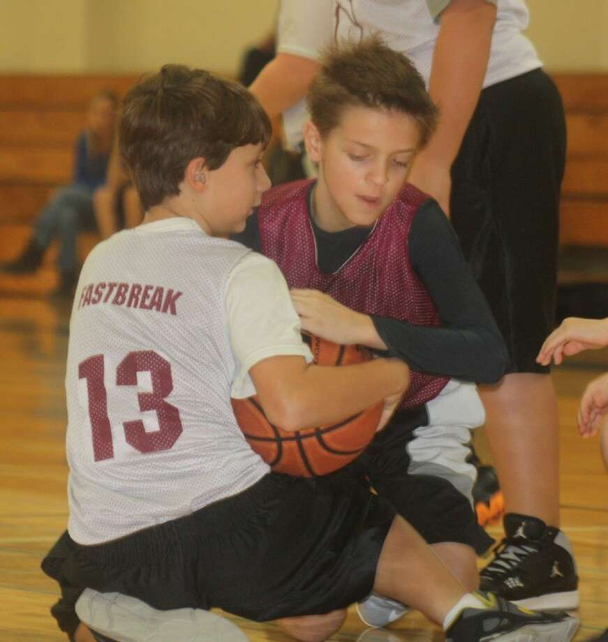 It's almost youth basketball season for Deer Park's youngsters. That means battles for the ball like this one from last year's campaign will become a regular sight on the various junior high courts later this month and in February. Photo: Robert Avery