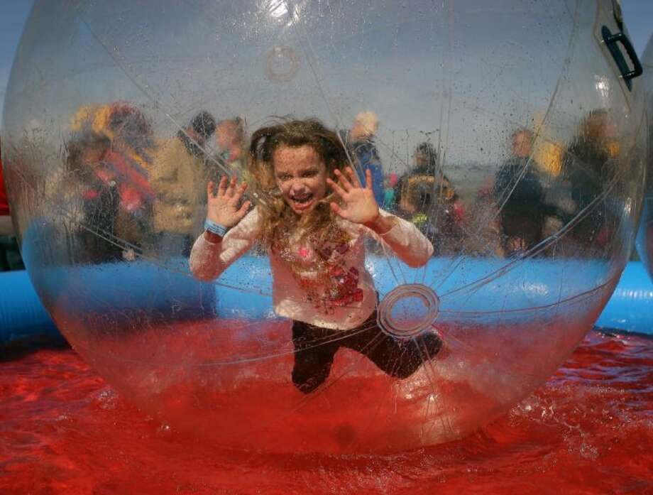 Nine-year-old Veronica jumps inside of a bubble as she tries to navigate on the water which was one of the attractions that drew long lines during Winterfest in Pearland.