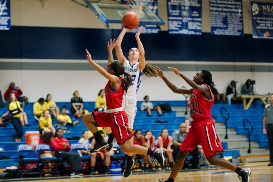 Friendswood's Maggie Roher (22) puts up a shot over Clear Brook's Cheron Galloway (15) and Na'Kayla Davis (34) in a District 24-6A game won by Friendswood, 42-31. Photo: KIRK SIDES