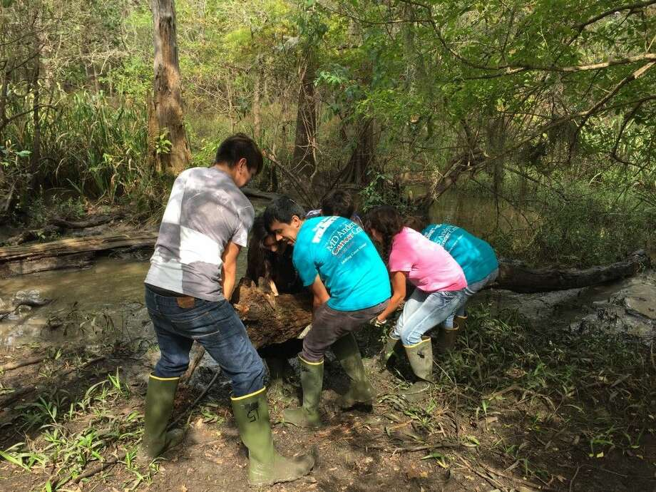 Students from Liberty High School lift and remove a log from Knobby Knees Trail. Photo: Submitted