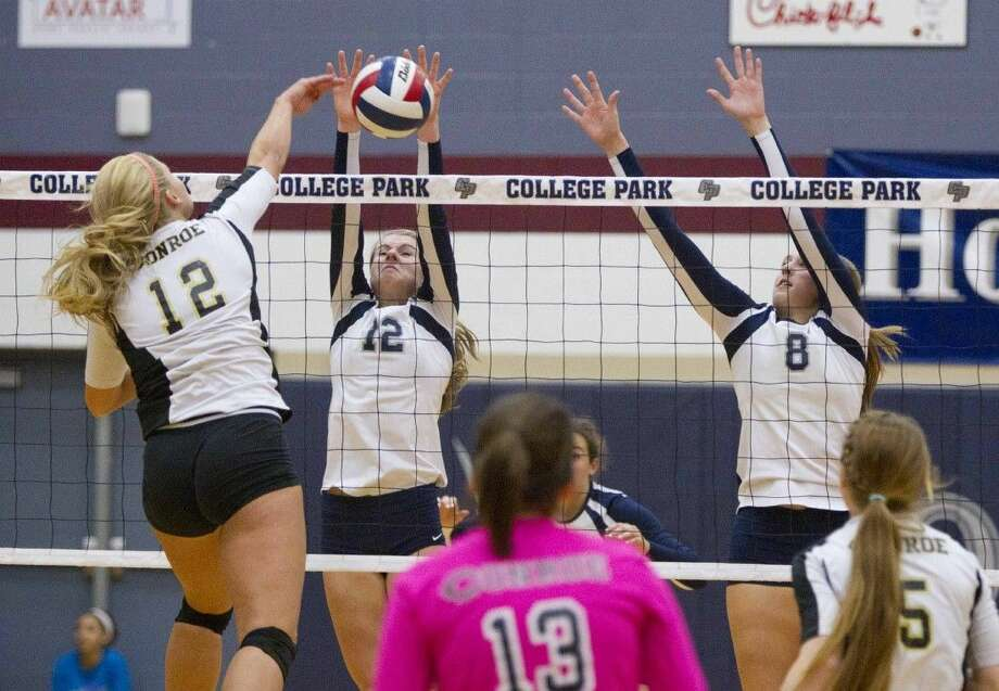 College Park's Julianna Waller and Haley Sobosle block a shot by Conroe's Aubrey Ireland during a high school volleyball game at College Park High School Friday. To view or purchase this photo and others like it, visit HCNpics.com.