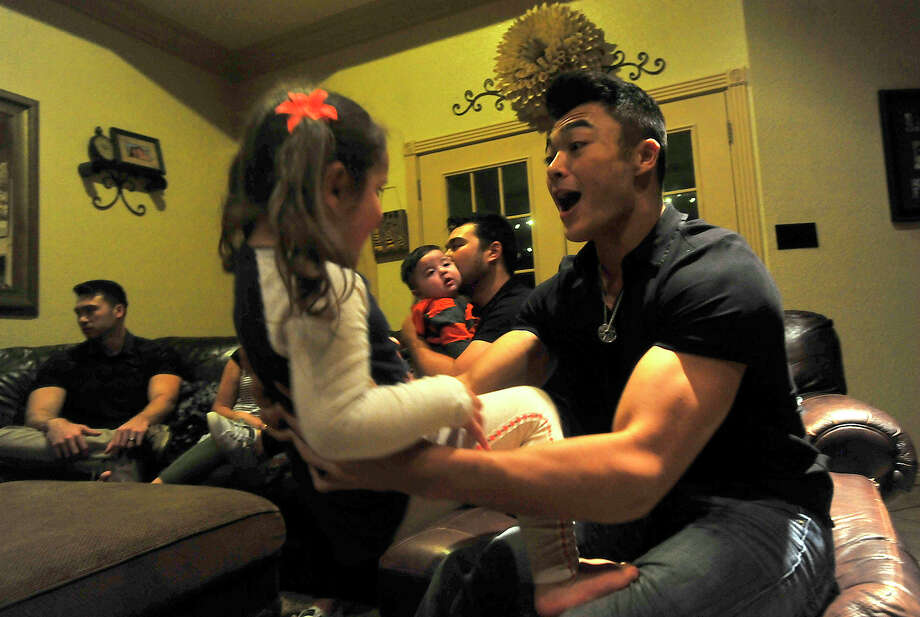 Vidor senior football player Maverick Quirante plays with his niece Arianna, 3, while the family gather at their parents' home in Vidor Wednesday night. The Quirantes, who are Mormon, have a large family, and all the children have been stand-outs in high school athletics. Photo taken Wednesday, October 5, 2016 Kim Brent/The Enterprise Photo: Kim Brent / Beaumont Enterprise