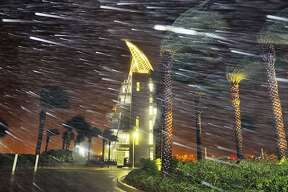 Trees sway from heavy rain and wind from Hurricane Matthew  in front of Exploration Tower early Friday, Oct. 7, 2016 in Cape Canaveral, Fla.   Matthew weakened slightly to a Category 3 storm with maximum sustained winds near 120 mph, but the U.S. National Hurricane Center says it's expected to remain a powerful hurricane as it moves closer to the coast.  (Craig Rubadoux/Florida Today via AP)