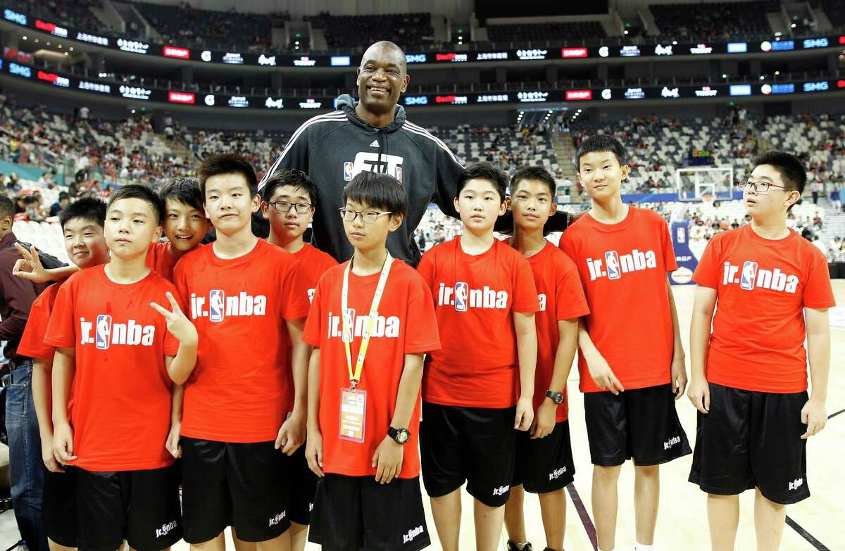 Former NBA basketball star Dikembe Mutombo has his photo taken with a group of Chinese students during a fan day event in Shanghai, China, Friday, October, 7, 2016. The Houston Rockets and the New Orleans Pelicans will play two NBA preseason games in Shanghai next week. (AP Photo)