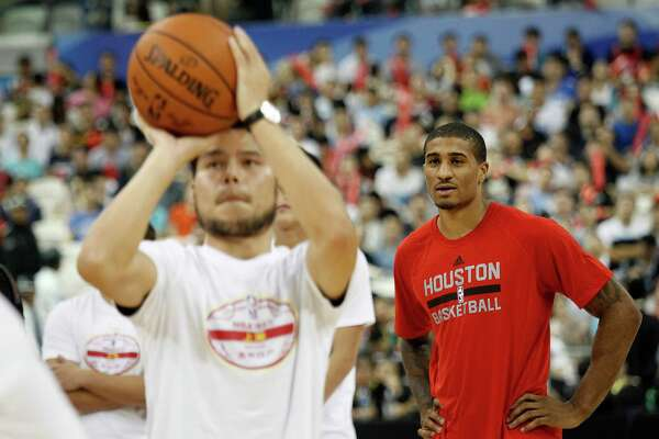 Gary Payton II of the Houston Rockets, right, watches a spectator shoot for a basket during a fan day event in Shanghai, China, Friday, October, 7, 2016. The Houston Rockets and the New Orleans Pelicans will play two NBA preseason games in Shanghai next week. (AP Photo)