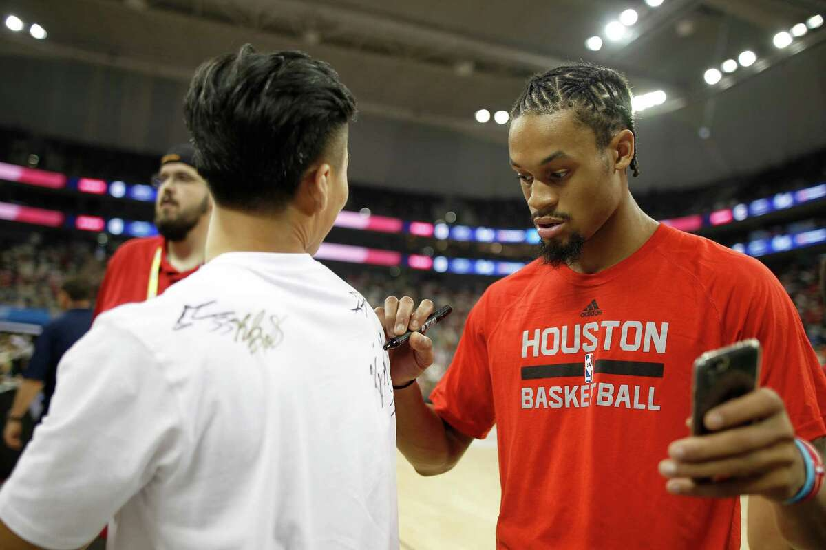 K.J. McDaniels of Houston Rockets signs his autograph on a spectators shirt during a fan day event in Shanghai, China, Friday, October, 7, 2016. The Houston Rockets and the New Orleans Pelicans will play two NBA preseason games in Shanghai next week. (AP Photo)