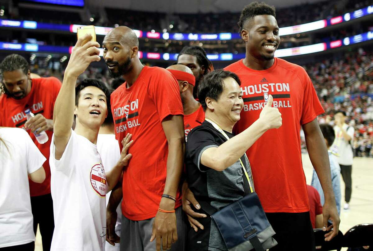 Houston Rockets players Corey Brewer, left, Chinanu Onuaku pose for photos during a fan day event in Shanghai, China, Friday, October, 7, 2016. The Houston Rockets and the New Orleans Pelicans will play two NBA preseason games in Shanghai next week. (AP Photo)