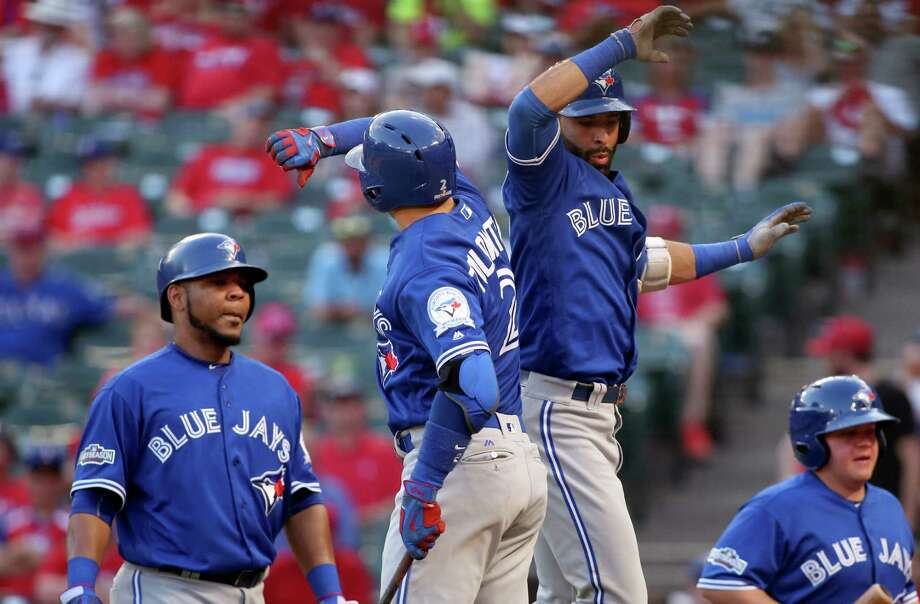 The Toronto Blue Jays' Troy Tulowitzki (2) and Jose Bautista (19) celebrate Bautista's three-run home run in the ninth inning against the Texas Rangers in Game 1 of the ALDS at Globe Life Park in Arlington, Texas, on Thursday, Oct. 6, 2016. The Blue Jays won, 10-1. (Richard W. Rodriguez/Fort Worth Star-Telegram/TNS) Photo: Richard W. Rodriguez, MBR / TNS / Fort Worth Star-Telegram