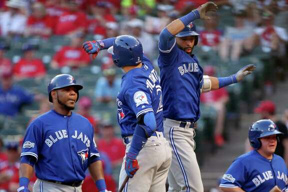 The Toronto Blue Jays' Troy Tulowitzki (2) and Jose Bautista (19) celebrate Bautista's three-run home run in the ninth inning against the Texas Rangers in Game 1 of the ALDS at Globe Life Park in Arlington, Texas, on Thursday, Oct. 6, 2016. The Blue Jays won, 10-1. (Richard W. Rodriguez/Fort Worth Star-Telegram/TNS)