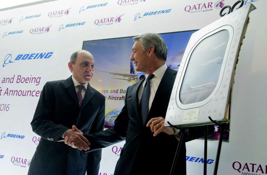 Akbar al Baker (left), CEO of Qatar Airways, and Ray Conner, CEO of Boeing's commercial airplane division, shake hands after announcing an $18.6 billion purchasing deal for 100 airplanes. Photo: Saul Loeb /AFP /Getty Images / AFP or licensors