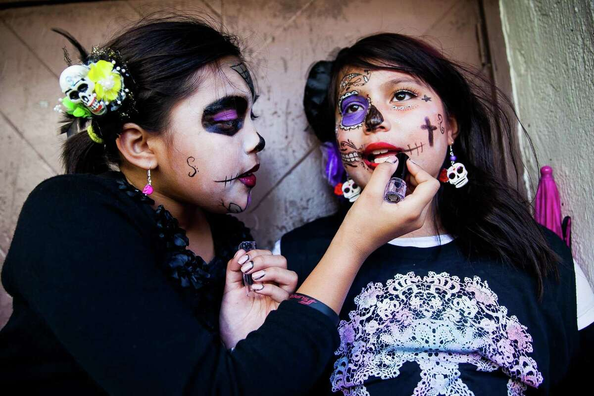 Serinah Rodriguez, 11, reapplies red lipstick on her cousin Jada Vega, 7, during the 2015 Día de Los Muertos-Muertos Fest held at La Villita.