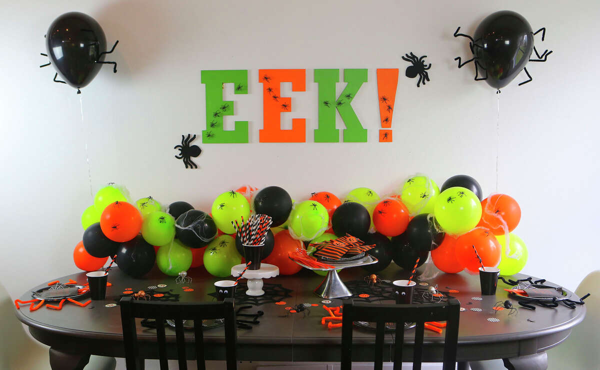 """Halloween is a great time to entertain. With just a little creativity you can transform your dining room table into a creepy crawly setting that will make your guests say """"Eek!""""I made a simple balloon garland centerpiece, an """"EEK!"""" party sign out of letters from the craft store, and gave paper plates and cups a Halloween makeover with pipe cleaners and googly eyes!"""