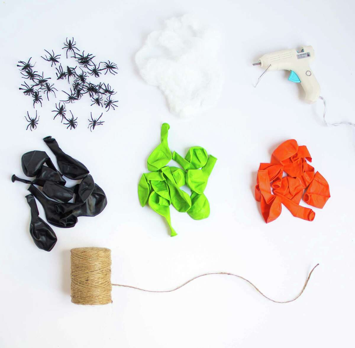 Materials 9- or 12-inch latex balloons in orange, black, and lime green (1 package of each is enough) Jute twine or string Small plastic spiders (you can buy these in a pack of 144 from OrientalTrading.com) Faux spiderweb Hot glue gun