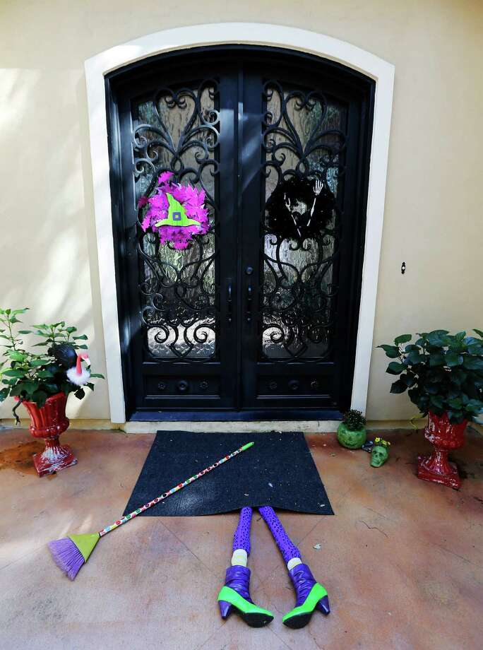 Morena Hockley creates three simple do-it-yourself products for Halloween to decorate a front door of a home. The three items are: a vulture made from a flamingo lawn ornament, the legs and broom of a witch for the front door welcome mat and two concrete planters in the shape of a jack-o-lantern and a skull. (Kin Man Hui/San Antonio Express-News) Photo: Kin Man Hui /San Antonio Express-News / ©2016 San Antonio Express-News